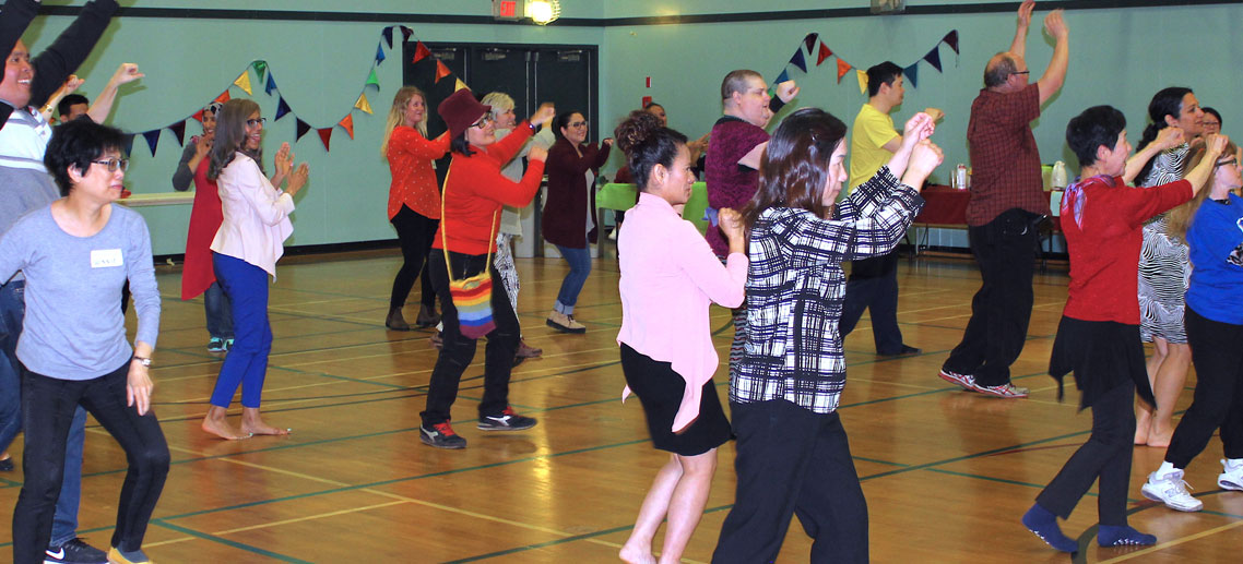 a large group of people of all races, genders, and ages dancing in a gymnasium