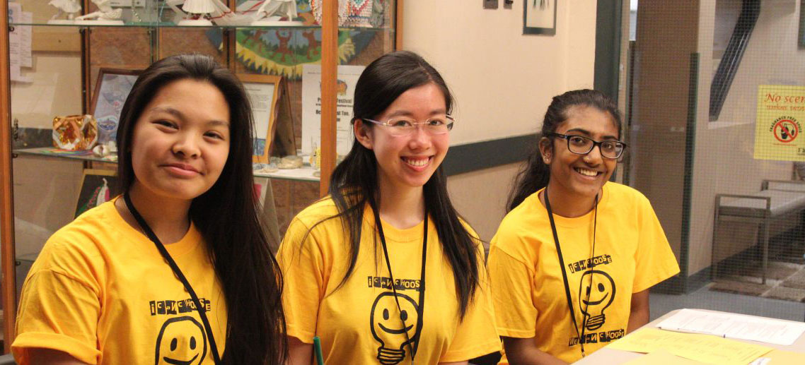 Three youth program volunteers wearing matching tshirts and sitting at a event registration table