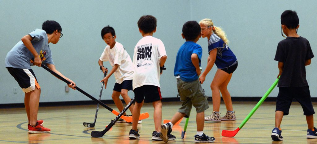 a group of kids playing hockey with plastic sticks in a gymnasium