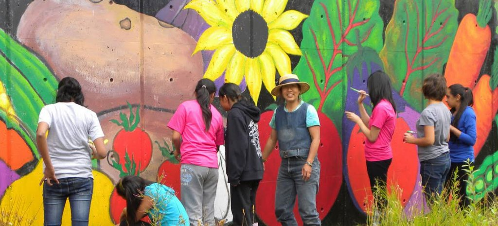 people standing along a wall as they paint colourful fruit, vegetables, and flowers on it