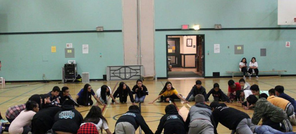 a large group of children in a gymnasium, sitting in a circle, about to play a game