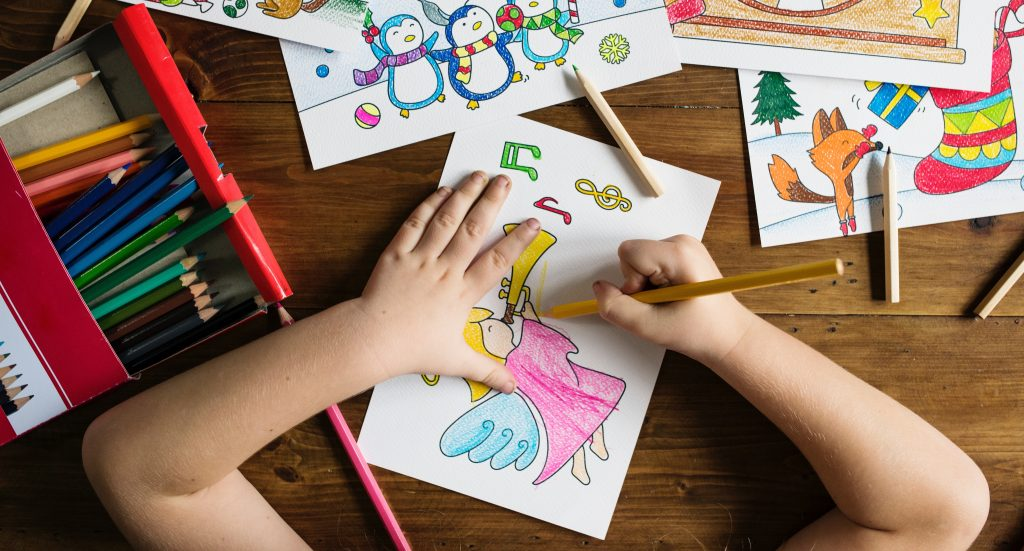 a child colouring a picture with pencil crayons