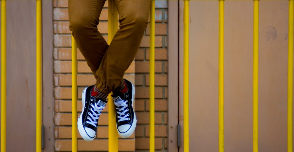 a young person with black canvas sneakers, sitting on a rail