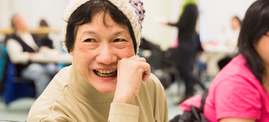 an older asian woman smiling at someone to her left