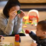 A mother holding a triangle and circle toy block with holes against her eyes and looking through at a child, holding a pentagon block.