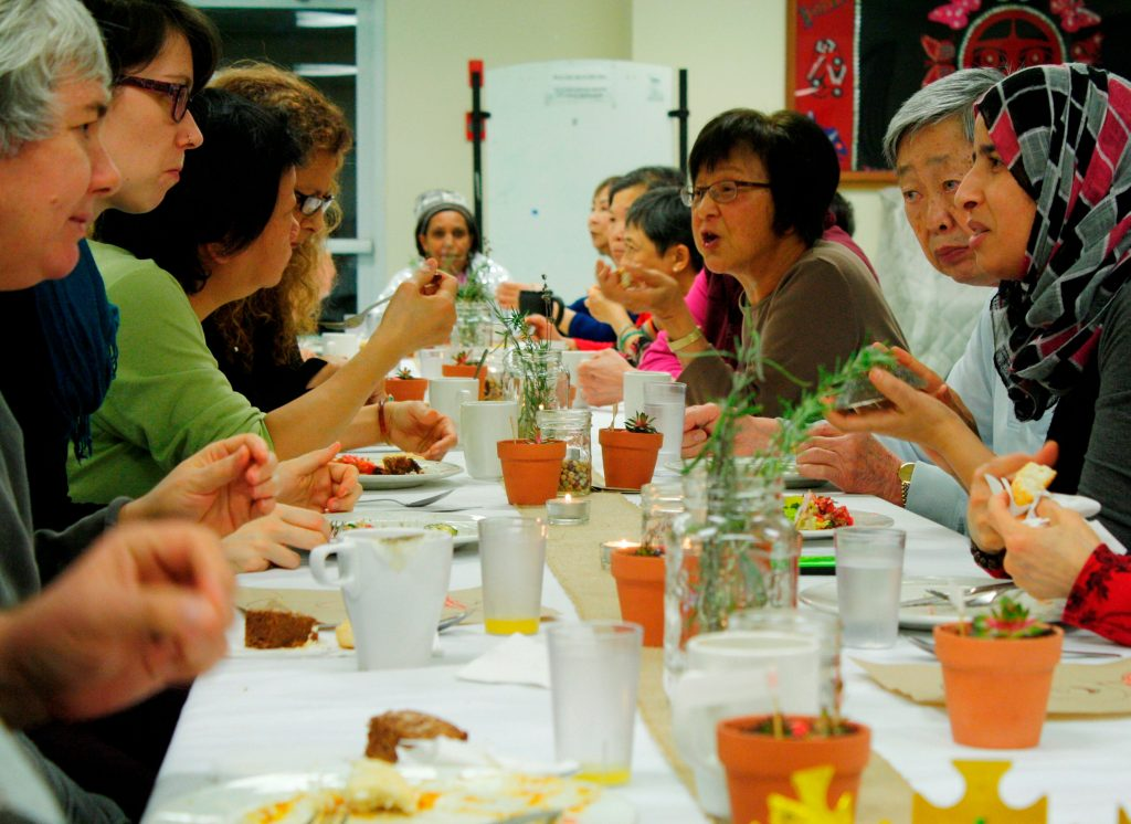 Food Security Program volunteers dining at a long table decorated with succulent plants and rosemary