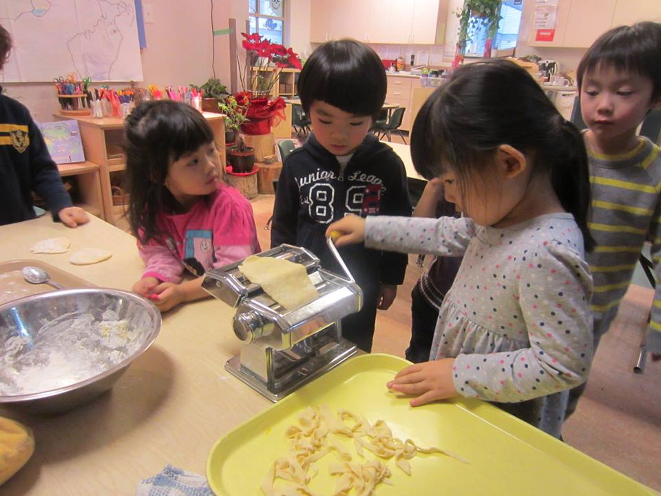 A child making homemade pasta using a pasta maker while five other children watch around a table.
