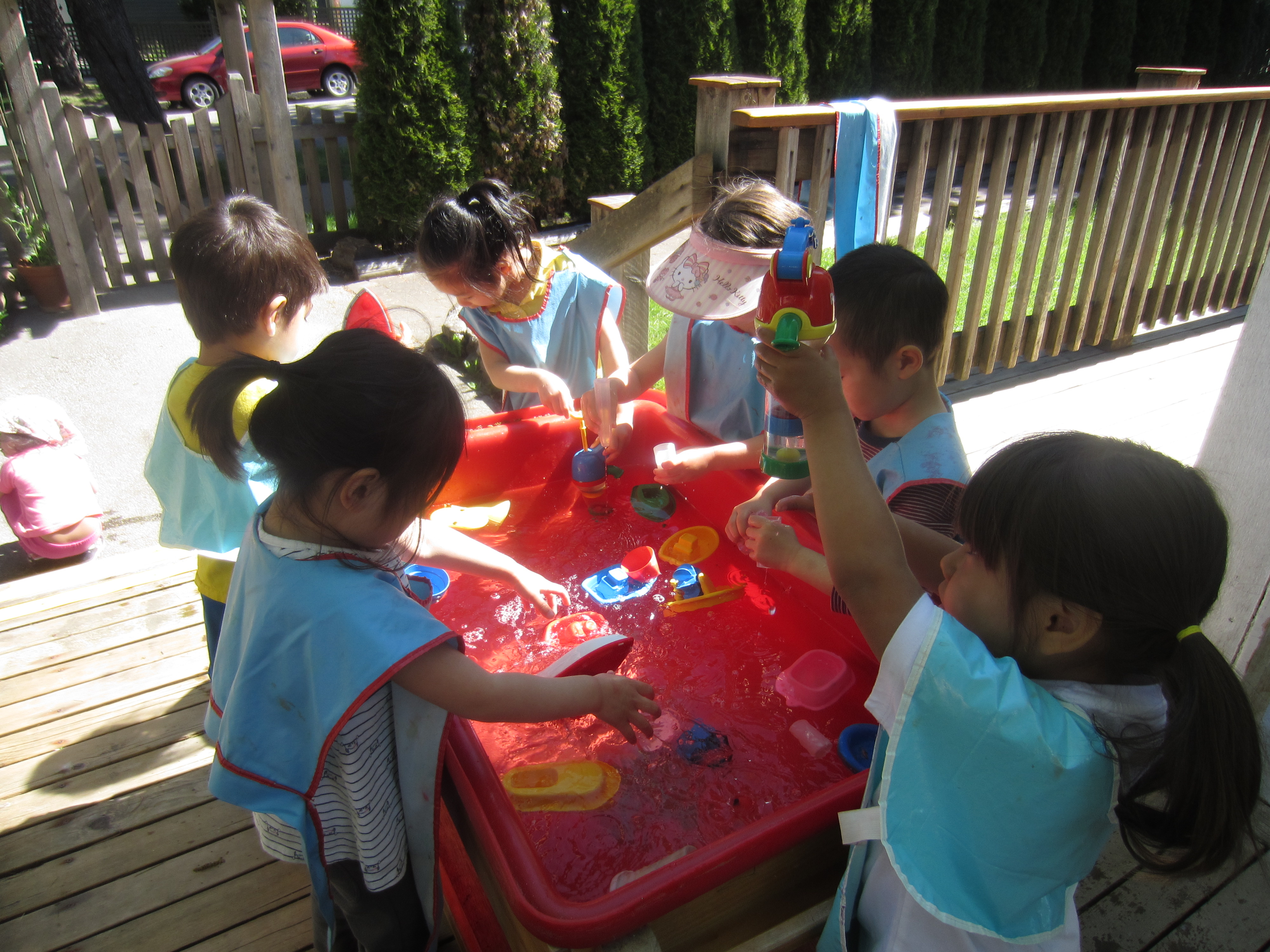 Six children playing around a large tub filled with water and floating toys.