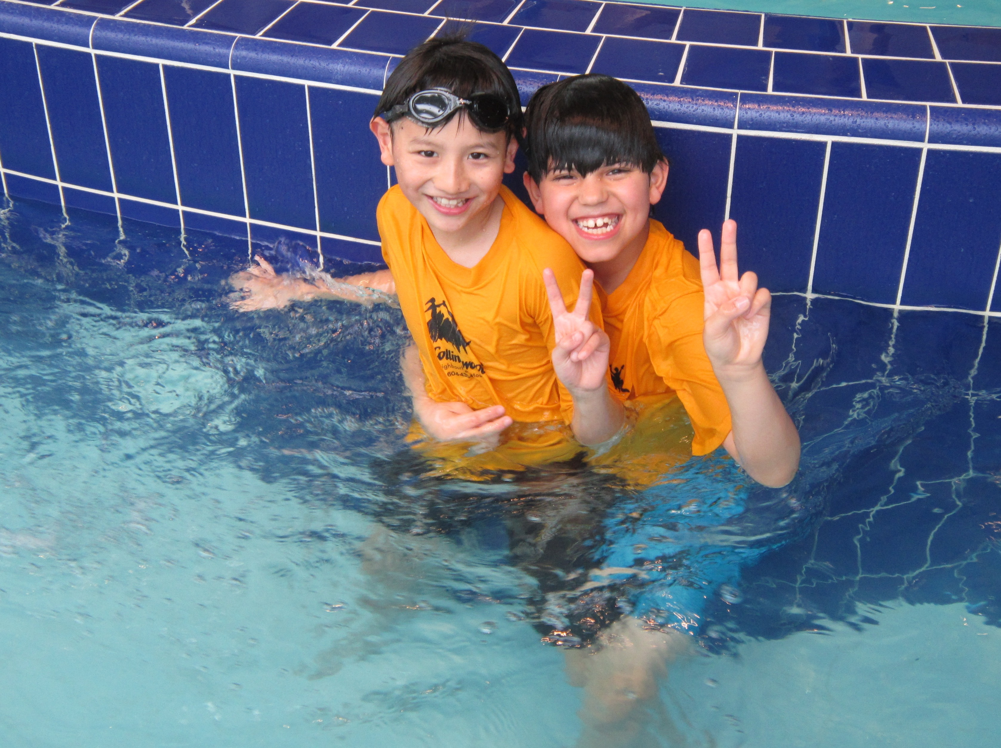 Two boys in a swimming pool hugging and smiling.