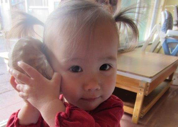 A toddler holding a large shell against her ear.