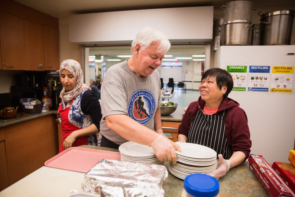Two seniors smiling and helping each other carry a stack of plates in the CNH kitchen. A staff person is in the background preparing for the Community Lunch program.