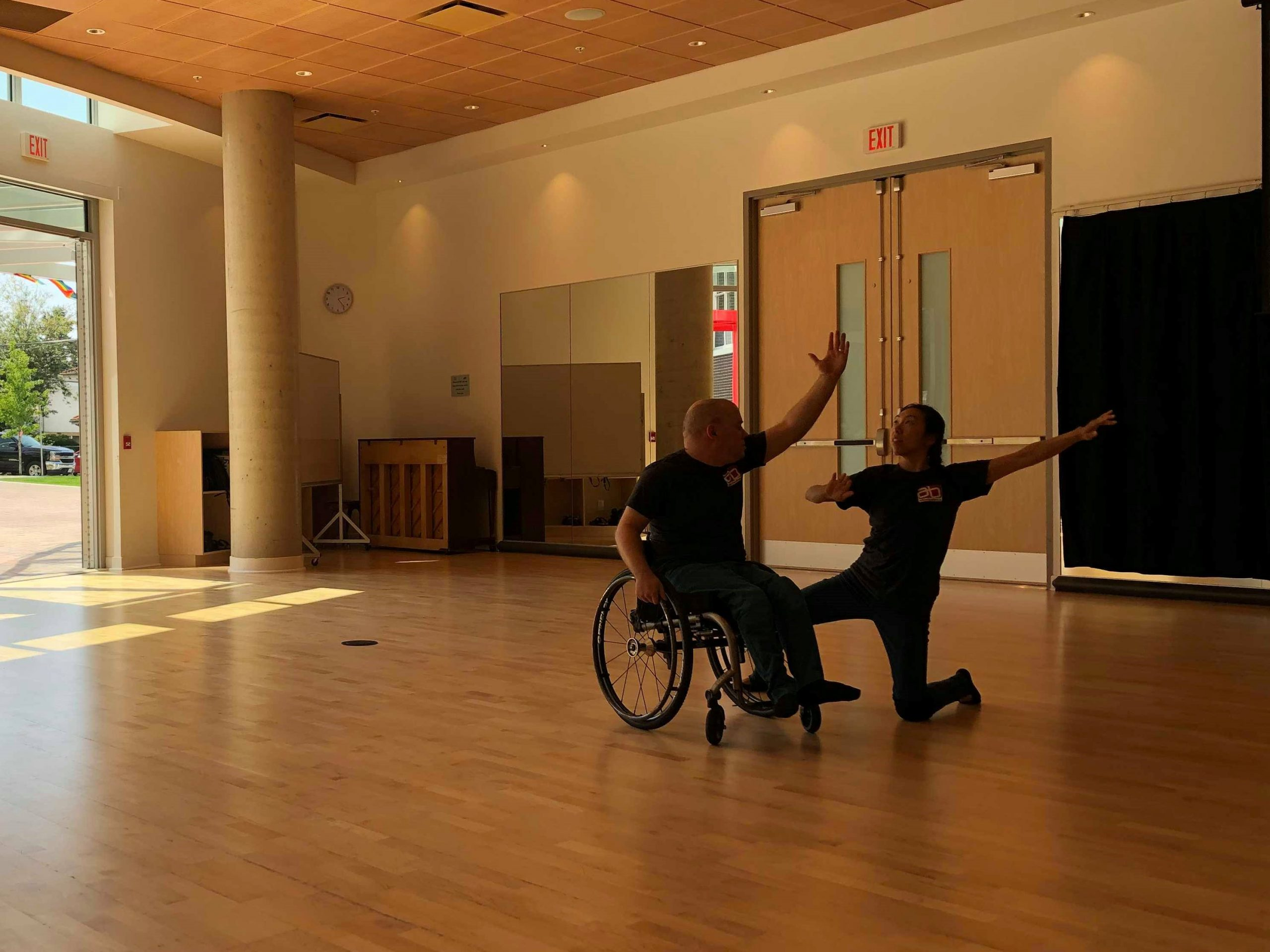 A woman and a man in a wheelchair are dancing together at the Annex Multipurpose room. The woman is kneeling next to the man and they both have one arm spread to the air.