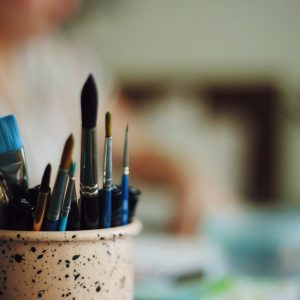 a closeup shot of a cup holding markers and paintbrushes