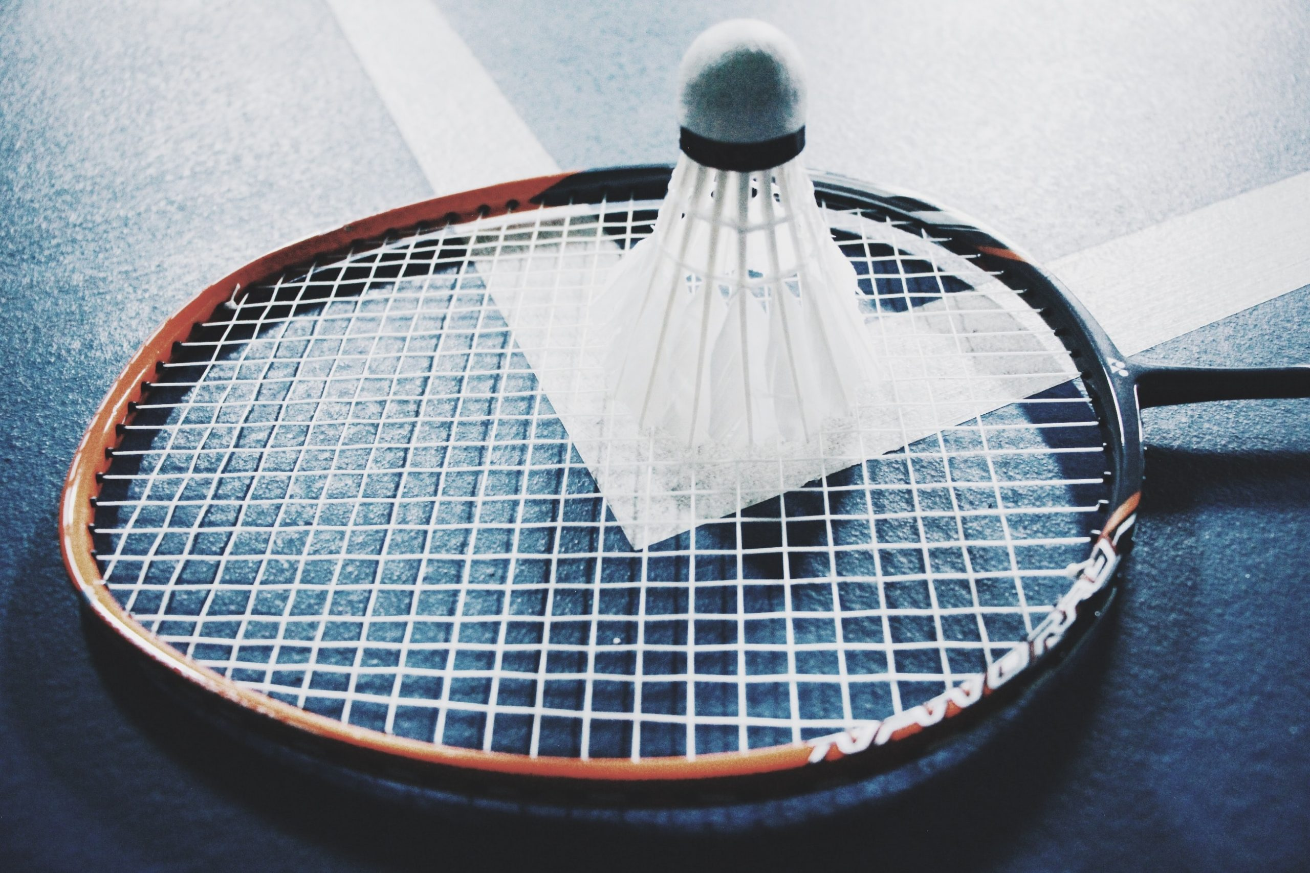 a shuttlecock on top of the badminton racket