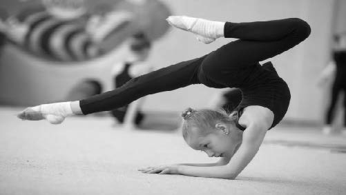 A young girl doing rhythmic gymnastics. She is upside down and balancing on her forearms and her legs are arranged into the splits