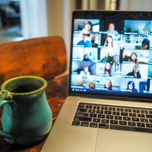 A laptop is on a table and shows an online Zoom meeting. There is a ceramic cup next to the laptop.