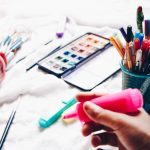markers, watercolour paints and brushes are arranged on a white cloth. A hand is holding a bright pink highlighter.
