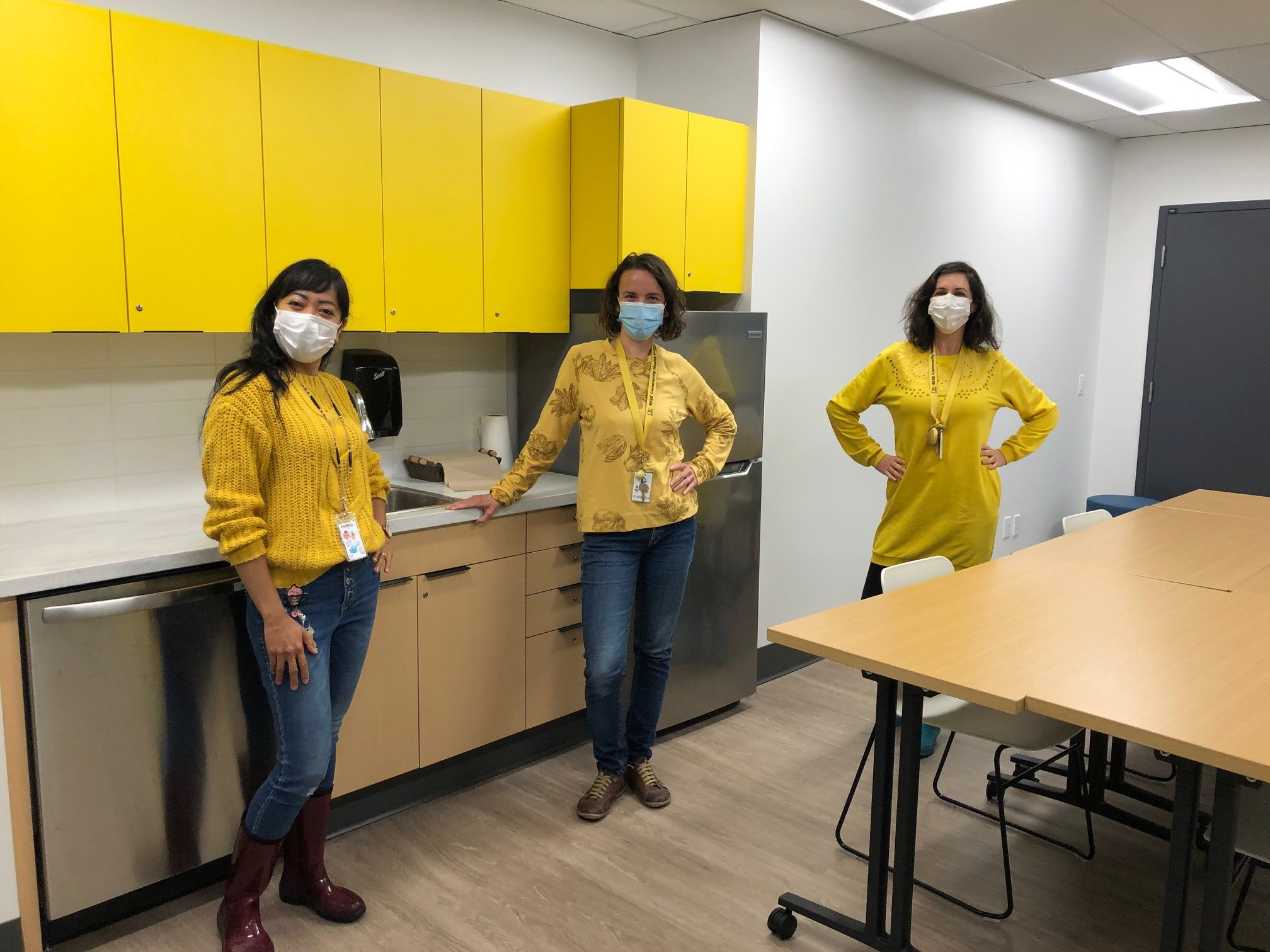 Three workers in wearing matching yellow tops and wearing masks in the RISE staff lounge.