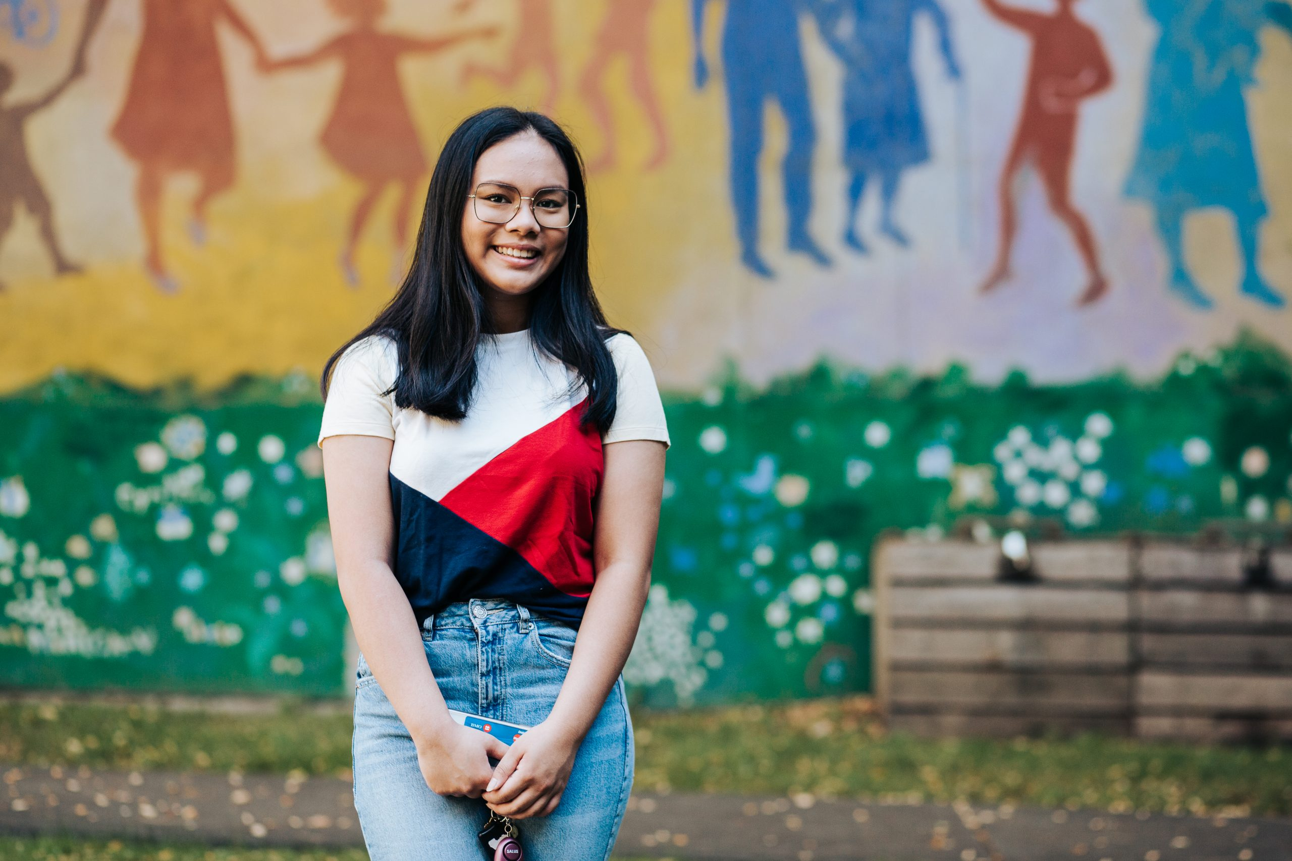 Richelle Tiongson stands in front of a colourful mural outside CNH.