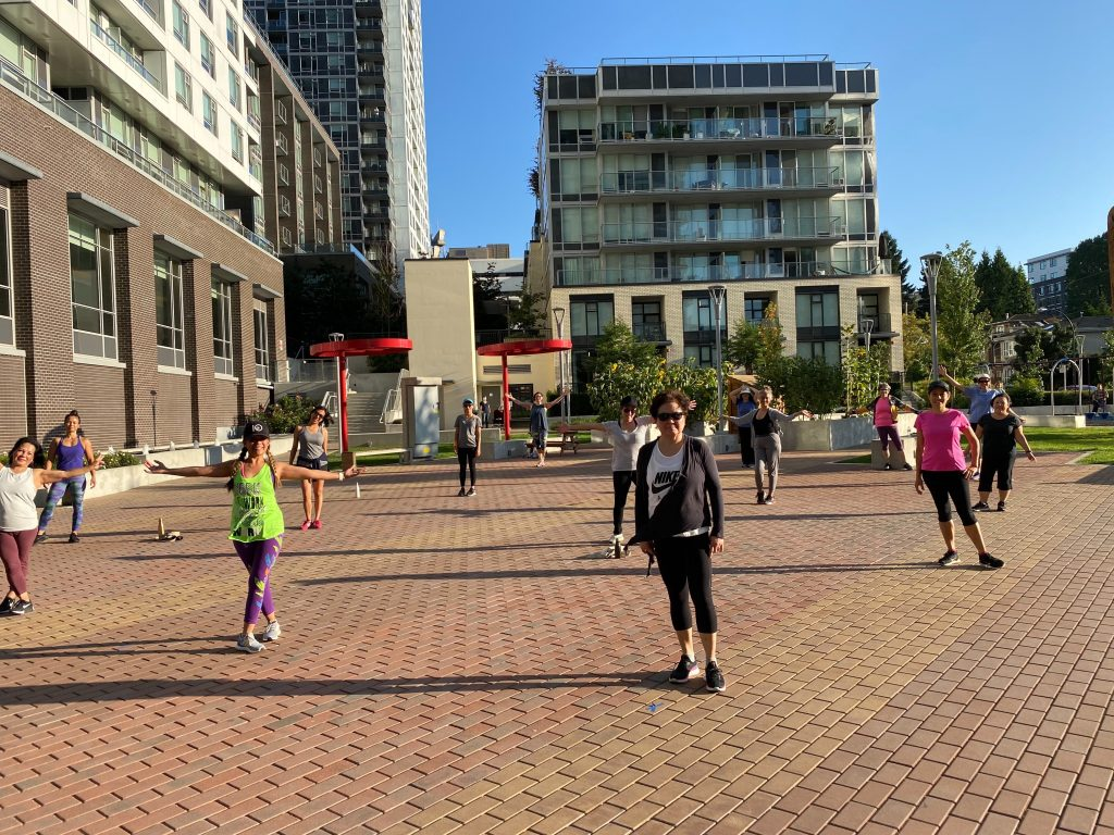 Large group of zumba participants doing zumba dance in an outdoor plaza outside of the CNH Annex
