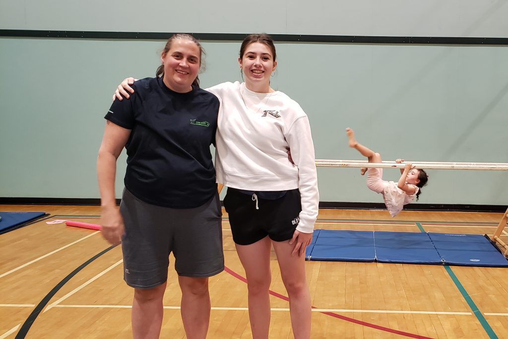 Lucinda Donaldson and Kyla Hanlon stand inside a gym. Kyla's arm is over Lucinda's shoulder.