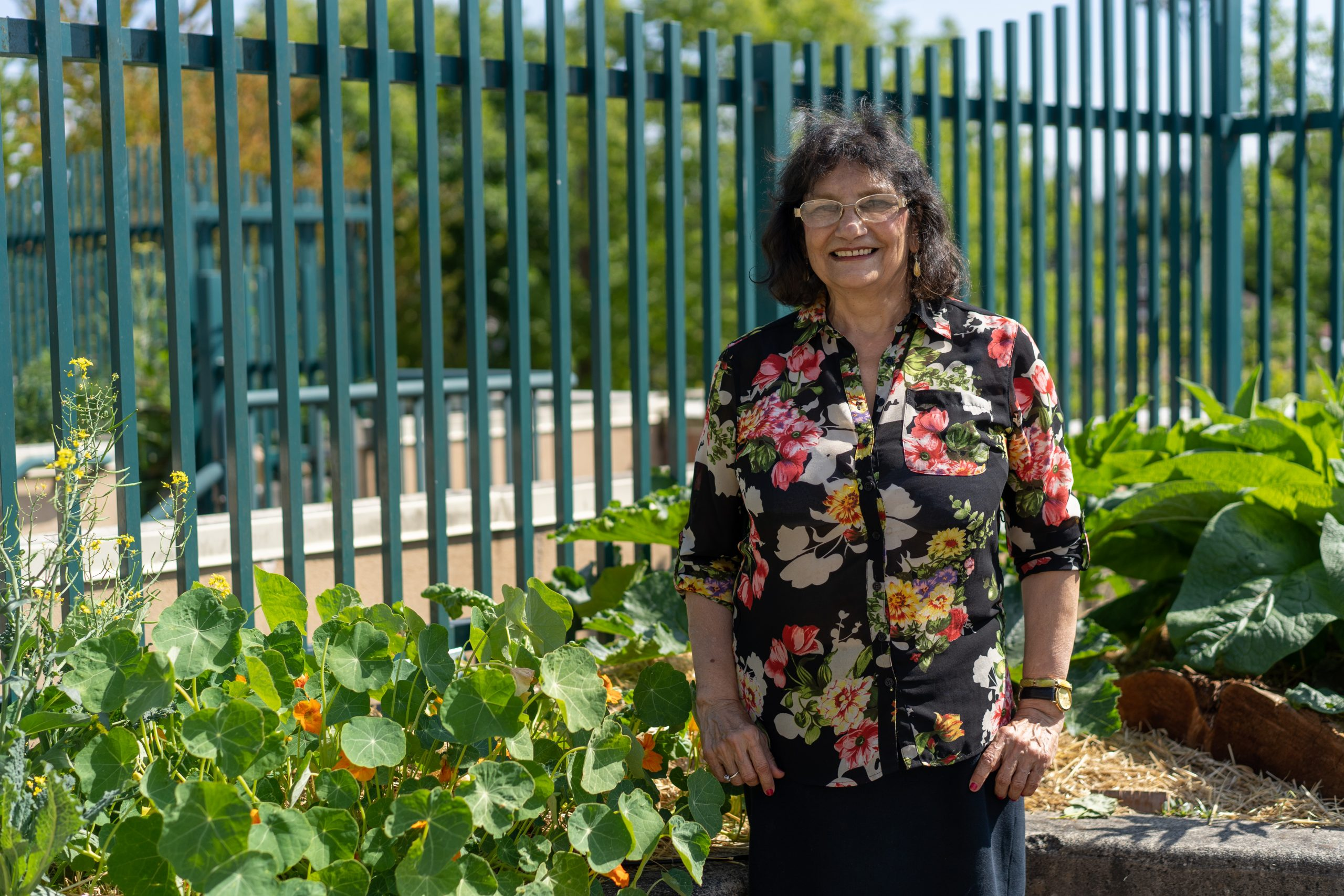 A volunteer standing in the rooftop garden and smiling. She is wearing a black top with red flowers.
