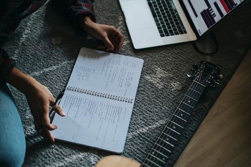 A person sitting on a rug writing in a notebook. They are lying next to a laptop and guitar