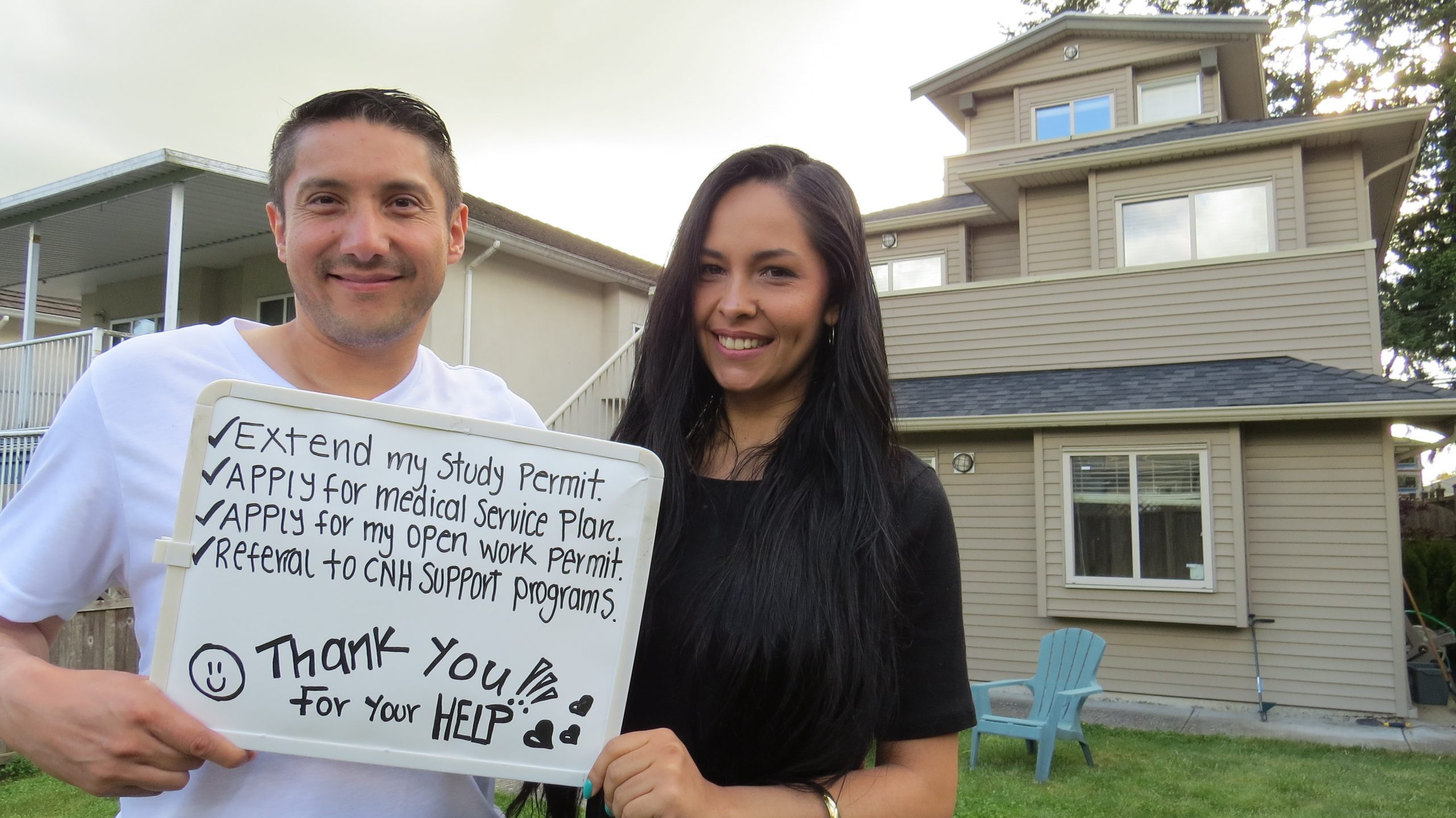 """A man and a woman outdoors in front of a house and holding a drawing board with """"Thank you for your help"""" on it."""