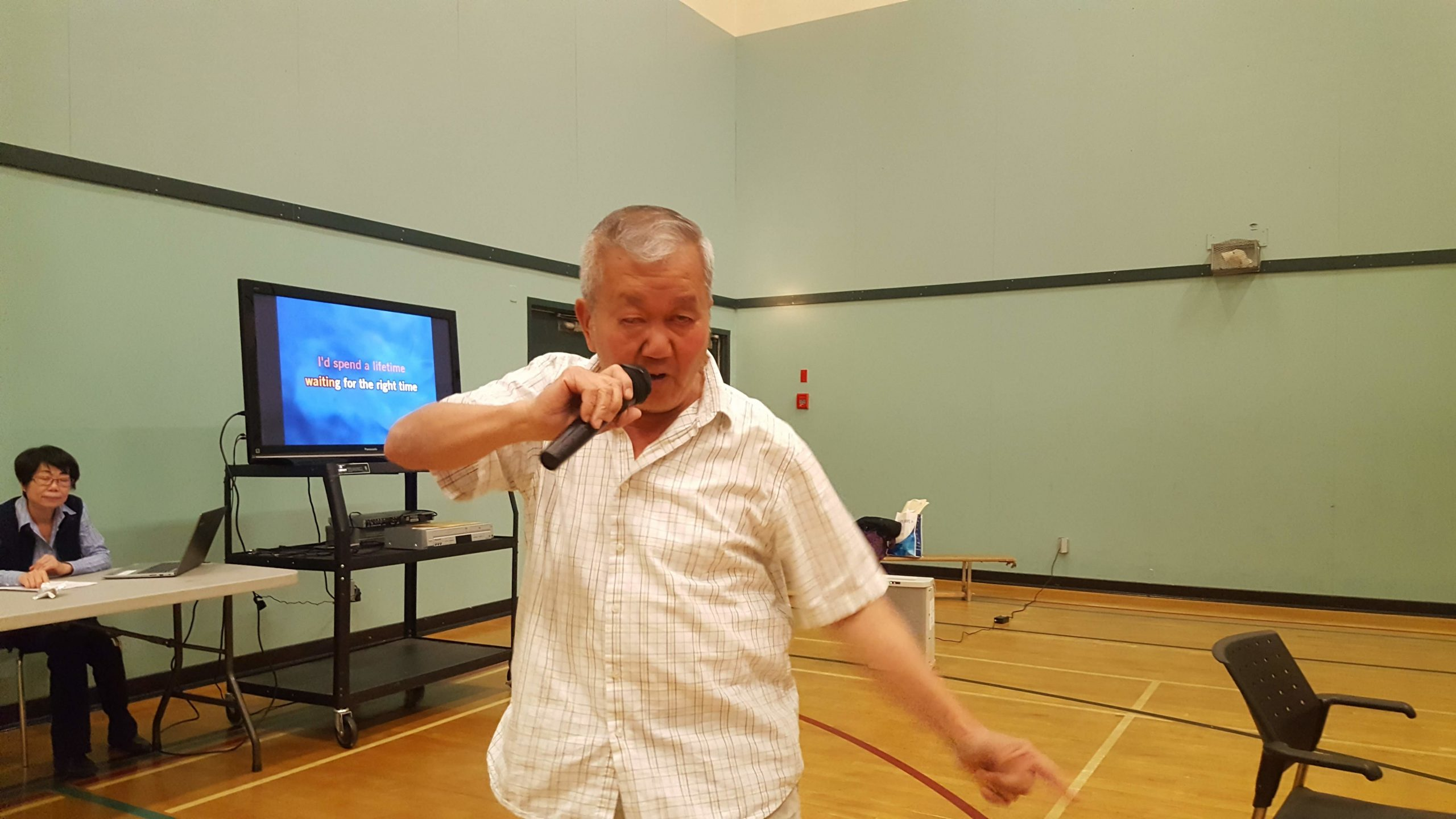 A man holds a microphone to his mouth inside a gymnasium