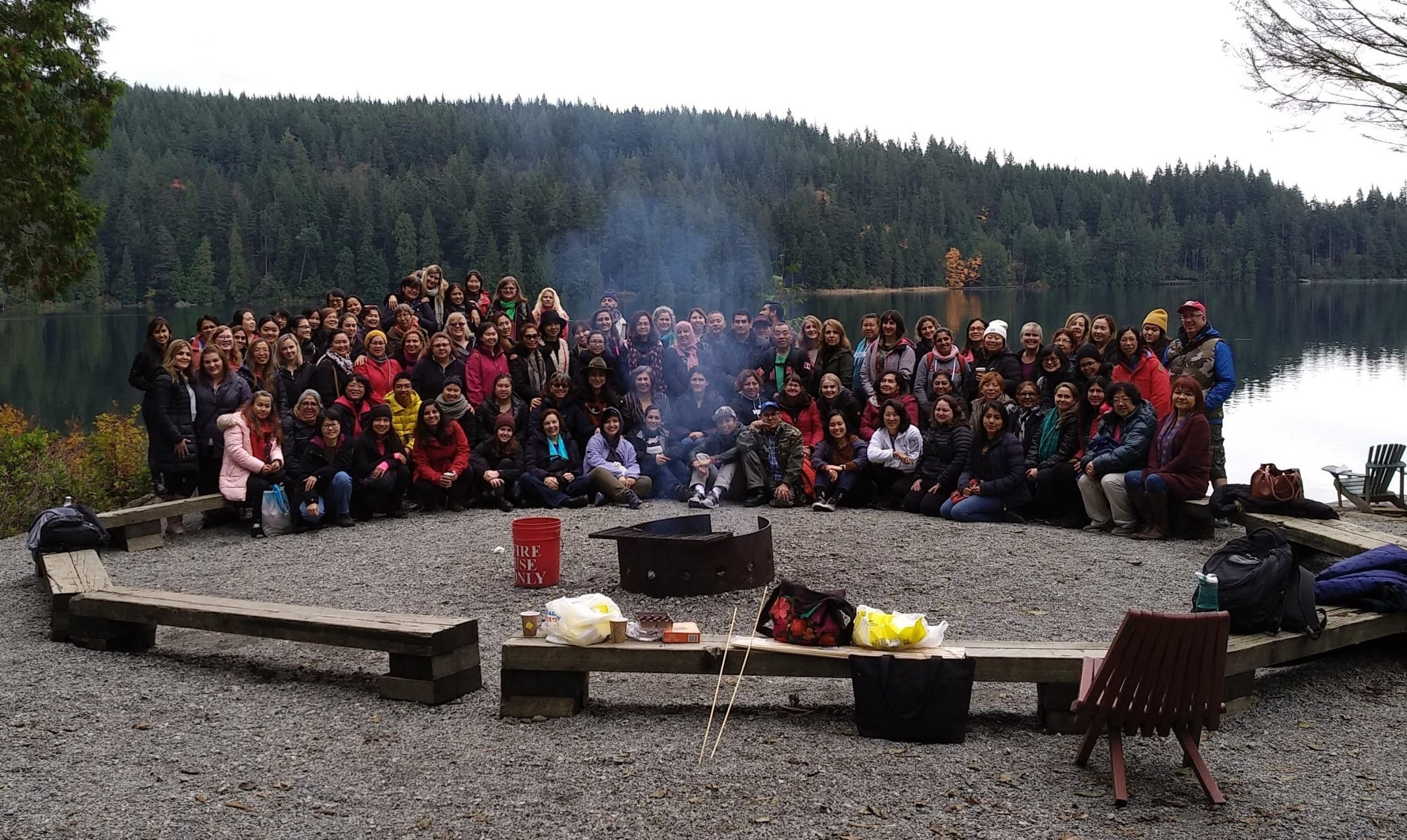 Large gathering of over 80 CNH staff in a semi-circle around the campfire next to a lake.