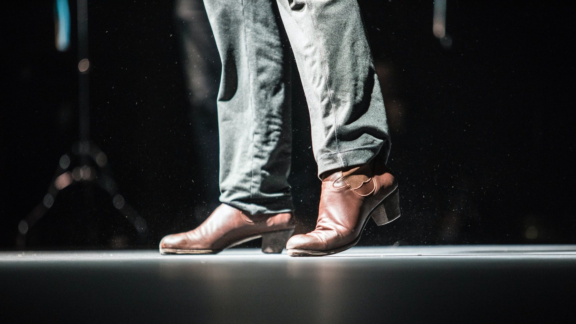 A pair of dark leather boots and jeans are lit by a spotlight indoors