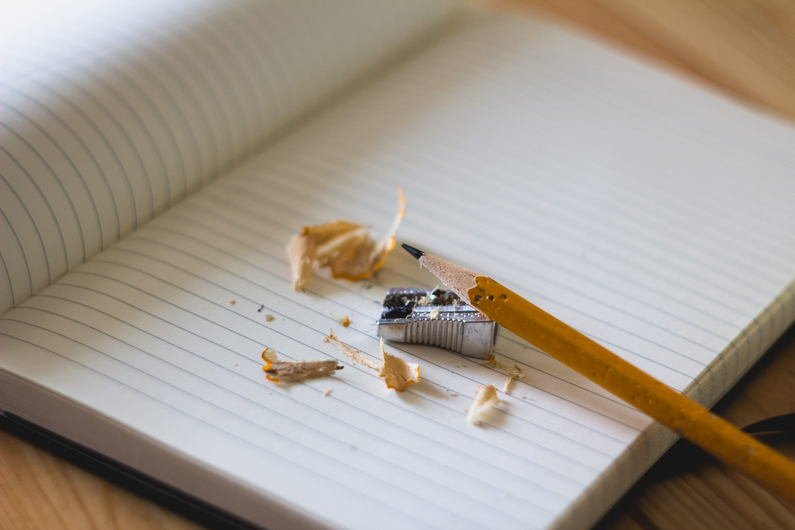 A pencil sits on top of an opened, lined notebook. Next to it is a sharpener and pencil sharpenings.