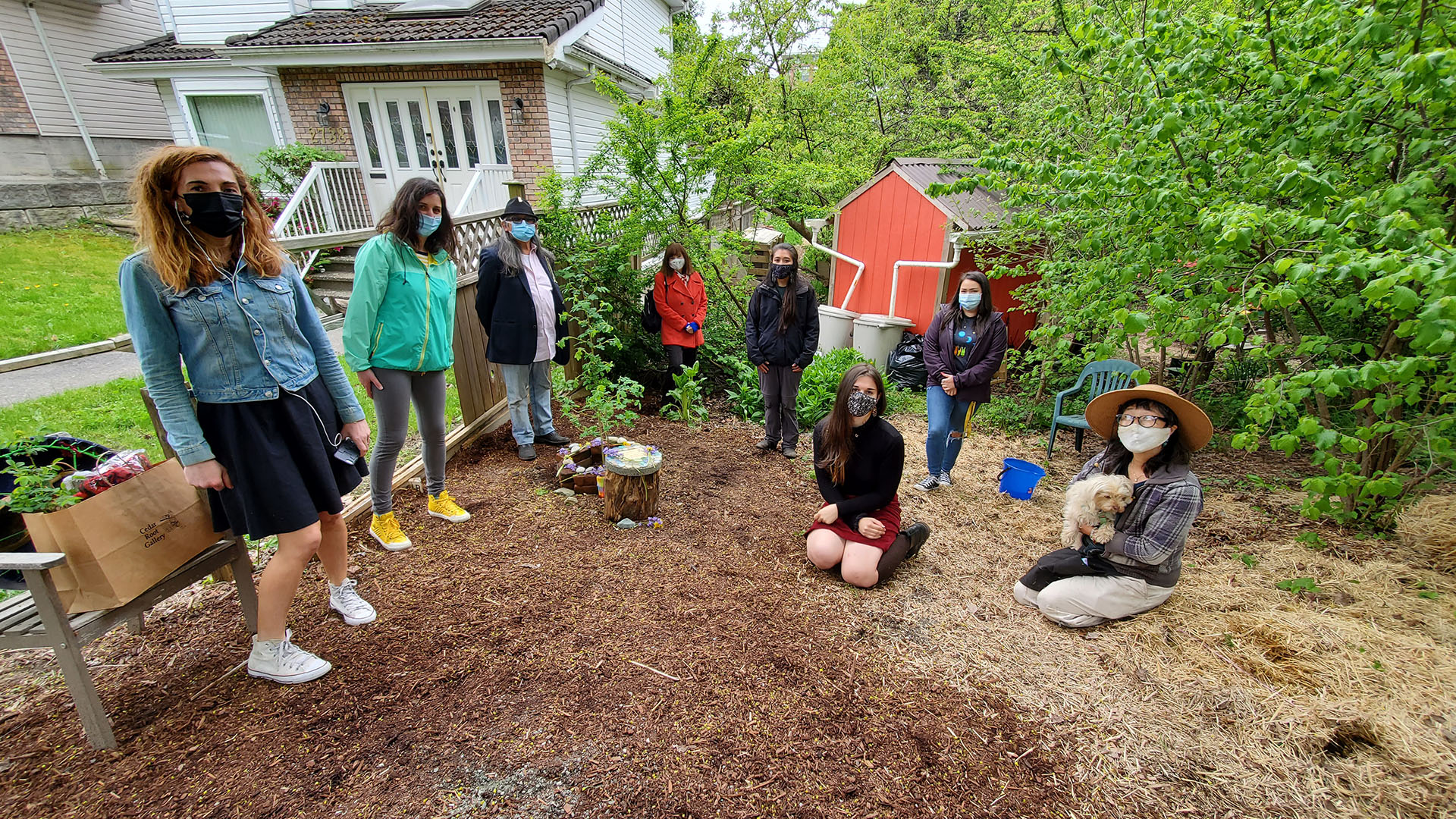 A group of eight adults are outdoors in a community garden