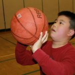 A young boy holds a basketball close to his face as he aims to throw it
