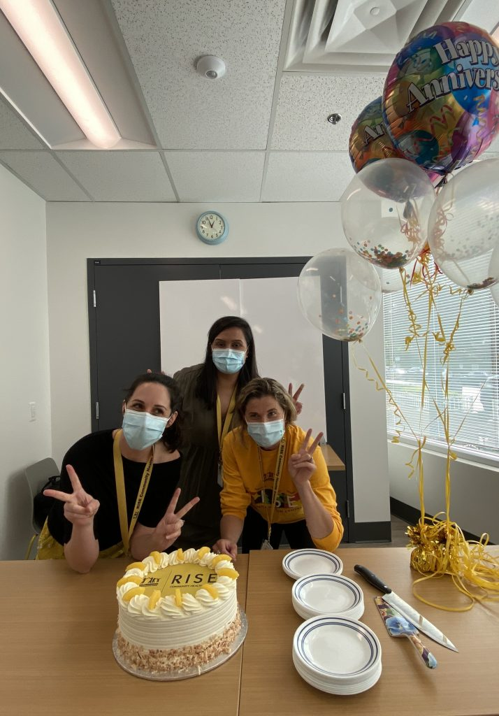 """Three people wearing face masks are indoors with a cake that reads """"RISE."""" To the right is a group of balloons."""