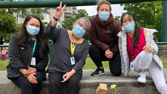 Four people sit together outside wearing face masks