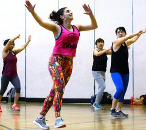 Zumba class at CNH. Participants are following the instructor and moving their arms in the air from side to side.