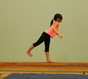 A young girl balances on one leg on a balance beam