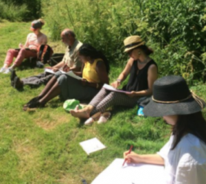 Five people sit on the grass holding notebooks