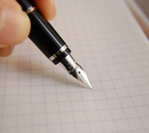 A black fountain pen is pressed against a grid paper